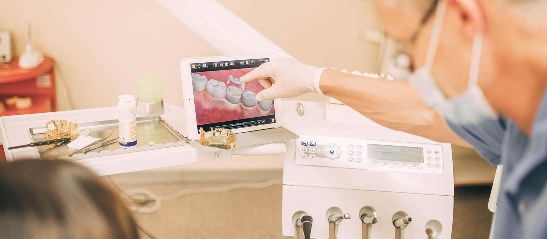 Zahnarzt Tino Helm erklärt Patientin Zahnersatz auf einem Tablet