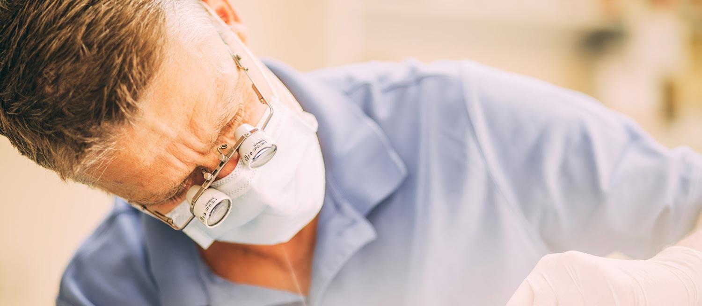 Zahnarzt Tino Nagel mit Vergrößerungslinse