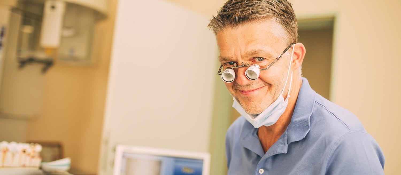 Zahnarzt Tino Nagel trägt eine Vergrößerungslinse und lächelt in die Kamera