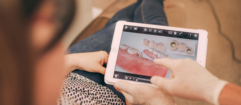 Mitarbeiterin erklärt Patientin Vorgehensweise einer Implantation.